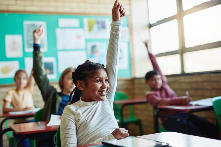 child with high self esteem raising hand in class